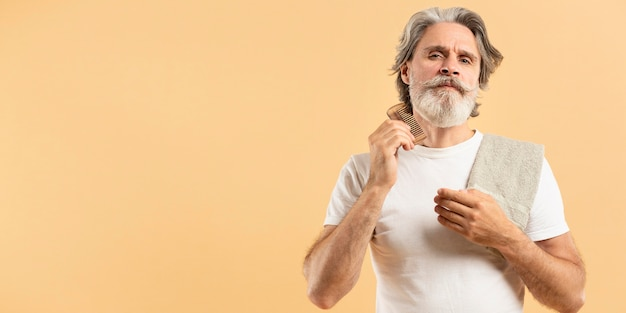 Uomo senior con l'asciugamano che pettina la sua barba