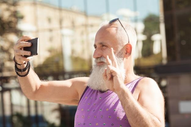 Uomo senior d'avanguardia che utilizza smartphone nel centro del centro all'aperto - maschio maturo di modo divertendosi con la nuova tecnologia di tendenze - tecnologia e concetto anziano allegro di stile di vita