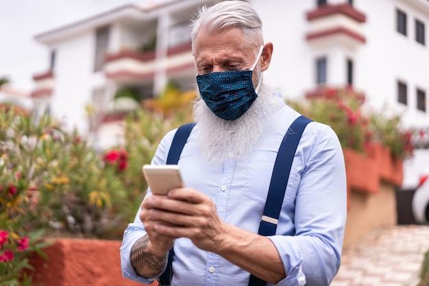 Uomo senior dei pantaloni a vita bassa che per mezzo del telefono cellulare astuto all'aperto mentre indossando la maschera di sicurezza del fronte
