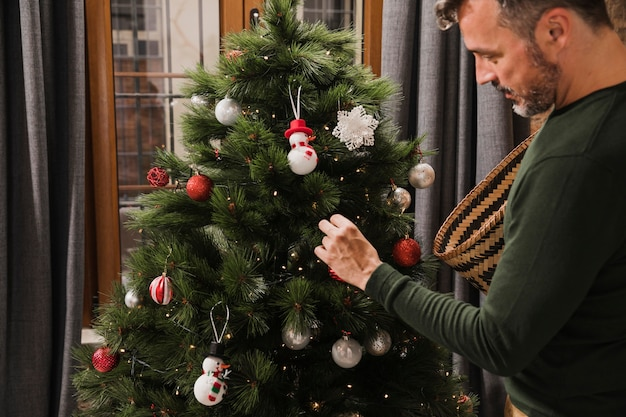 Uomo senior del colpo medio che decora l'albero di natale