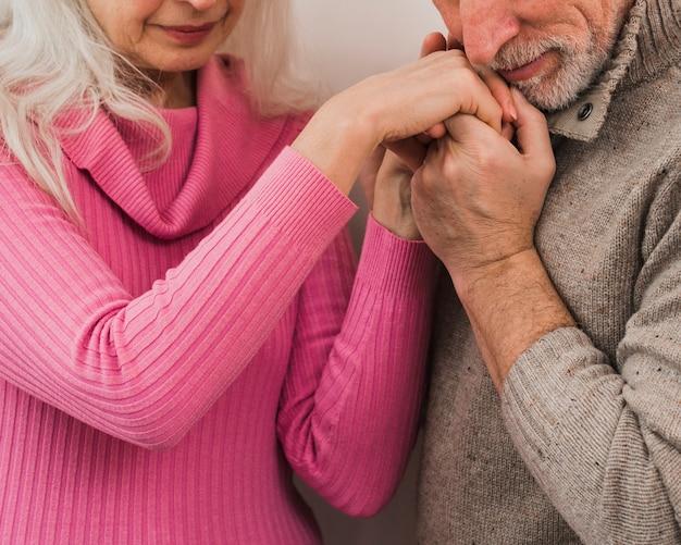 Uomo senior del primo piano che bacia le sue mani della moglie