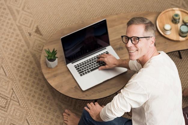 Uomo senior dell'angolo alto che per mezzo di un computer portatile