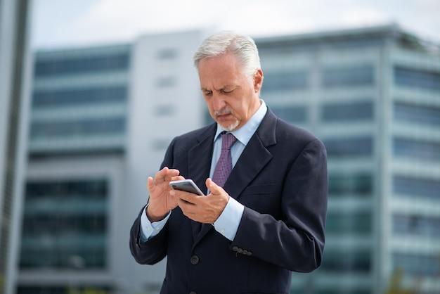Uomo senior di affari che per mezzo del suo smartphone all'aperto