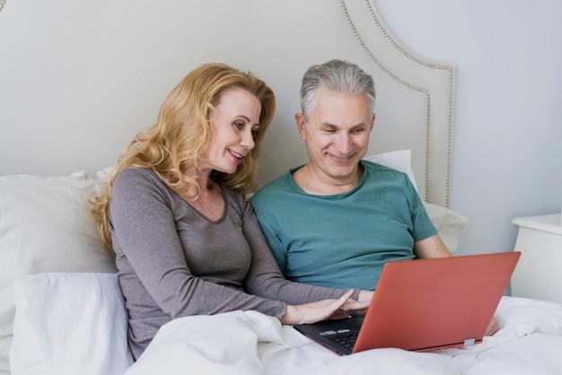 Uomo senior e donna adorabili con il computer portatile a letto