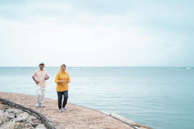 Uomo senior e donna che corrono insieme sulla spiaggia