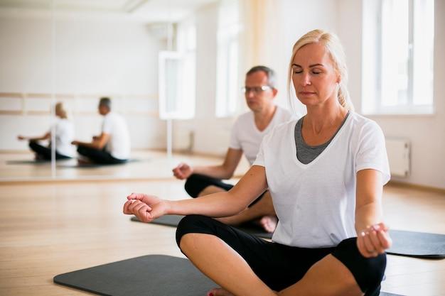Uomo senior e donna che meditano insieme