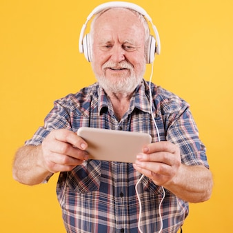 Uomo senior felice che guarda video musica