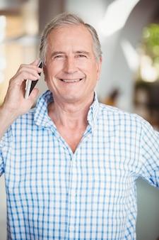 Uomo senior felice che parla sul telefono cellulare
