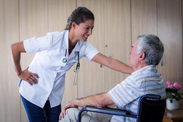 Uomo senior felice e medico che interagiscono nel salone