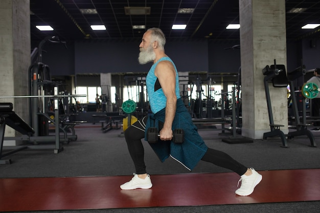 Uomo senior in abbigliamento sportivo in palestra che risolve con i pesi.