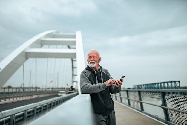 Uomo senior in abiti sportivi che per mezzo dello smartphone sul ponte nella città.