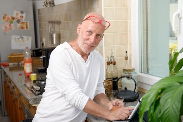 Uomo senior in cucina facendo uso della compressa digitale