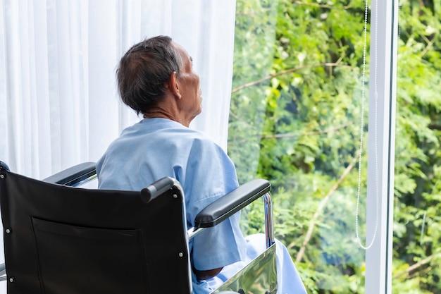 Uomo senior in sua sedia a rotelle con la schiena in ospedale.