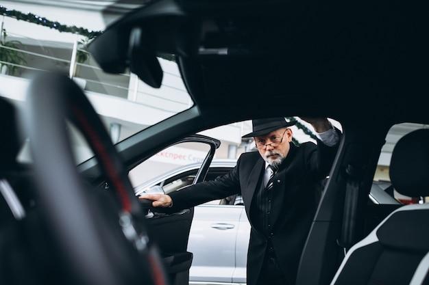 Uomo senior in una sala d'esposizione dell'automobile che sceglie un'automobile