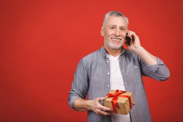Uomo senior maturo che mostra un regalo con il nastro rosso come presente isolato. usando il telefono.