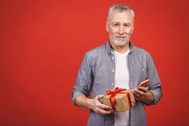 Uomo senior maturo che mostra un regalo con il nastro rosso come presente isolato.