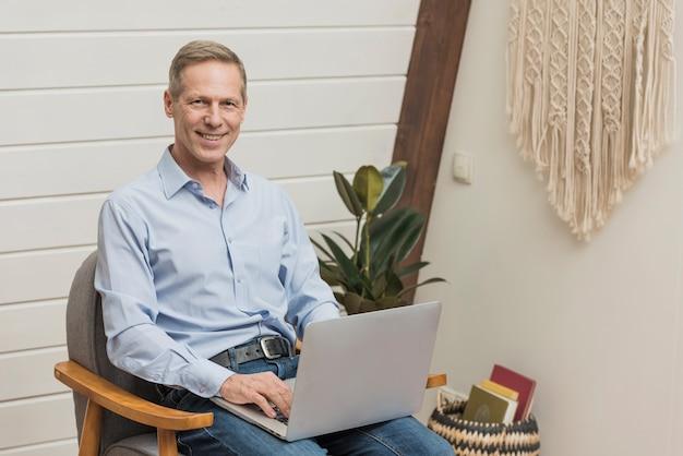 Uomo senior moderno che tiene un computer portatile