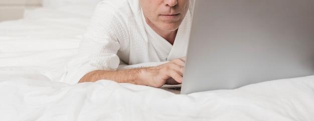 Uomo senior moderno che utilizza un computer portatile a letto