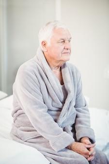 Uomo senior premuroso in accappatoio che si siede sul letto