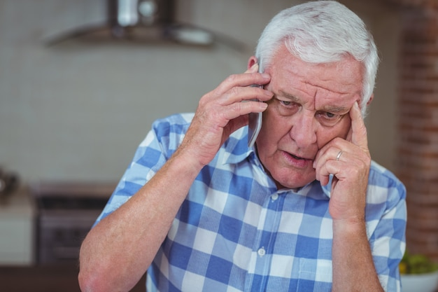Uomo senior preoccupato che parla sul telefono cellulare