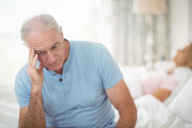 Uomo senior preoccupato che si siede nella camera da letto