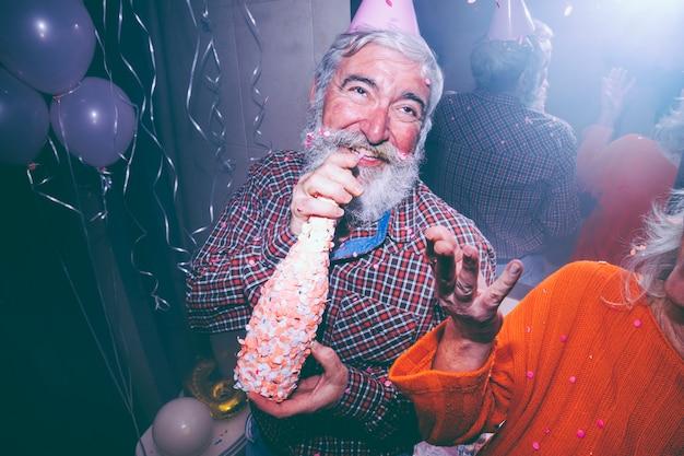 Uomo senior sorridente che giudica la bottiglia del champagne disponibila e sua moglie che gettano i coriandoli in aria