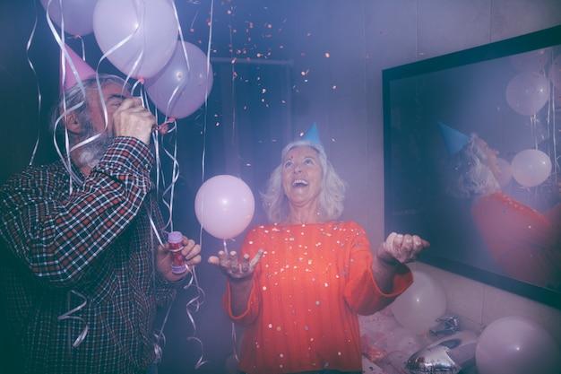 Uomo senior sorridente che soffia la bacchetta della bolla e sua moglie che gettano i coriandoli nella festa di compleanno