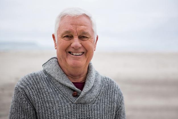 Uomo senior sorridente che sta alla spiaggia