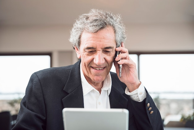 Uomo senior sorridente che utilizza telefono cellulare e compressa digitale nell'ufficio