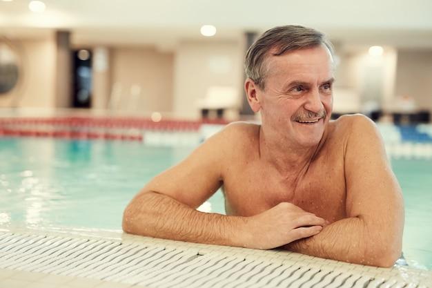 Uomo senior sorridente nella piscina