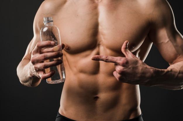 Uomo senza camicia atletico che indica alla bottiglia di acqua