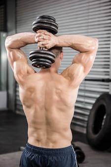 Uomo senza camicia che alza dumbbell pesante in palestra