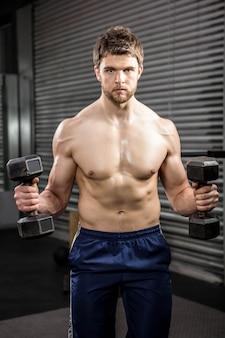 Uomo senza camicia che alza i dumbbells pesanti alla palestra del crossfit