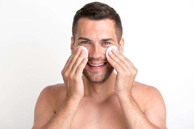 Uomo senza camicia che pulisce il suo fronte con i cuscinetti di cotone dell'ovatta sopra fondo bianco e che esamina macchina fotografica