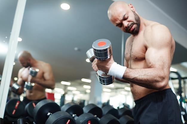 Uomo senza camicia che risolve con i pesi in palestra