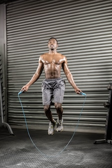 Uomo senza camicia che salta la corda in palestra