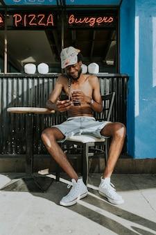 Uomo senza camicia che si siede in un caffè