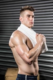 Uomo senza camicia con asciugamano intorno al collo in palestra