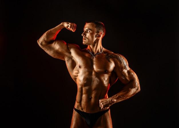 Uomo senza camicia con corpo muscoloso in topless alzando le braccia