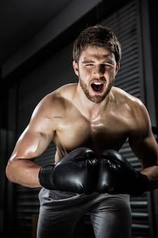Uomo senza camicia con i guanti boxe che gridano alla palestra di crossfit