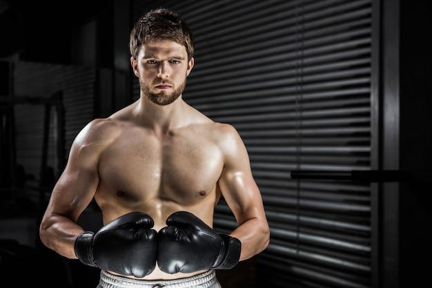 Uomo senza camicia con i guanti boxe nella palestra di crossfit