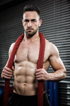 Uomo senza camicia con la corda di battaglia intorno al collo presso la palestra di crossfit