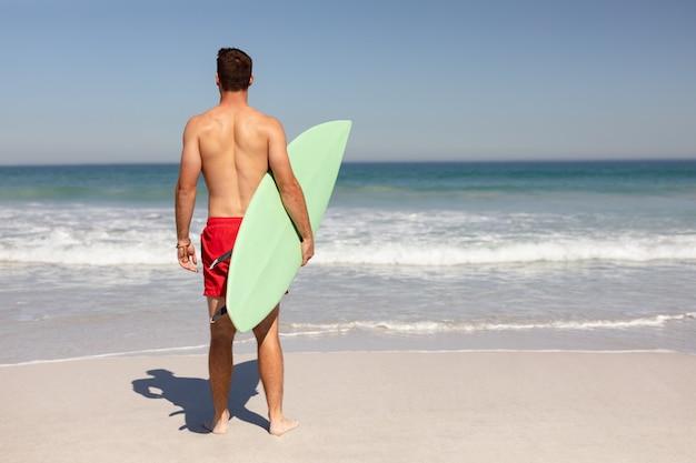 Uomo senza camicia con tavola da surf in piedi sulla spiaggia sotto il sole