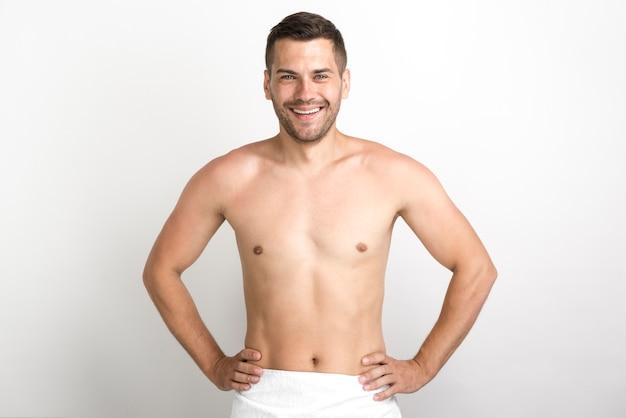 Uomo senza camicia felice che posa contro la parete bianca