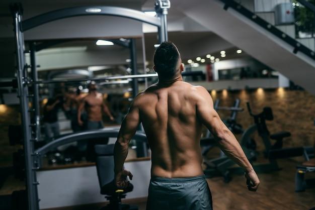 Uomo senza camicia muscolare che posa in palestra