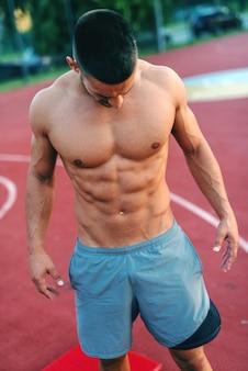 Uomo senza camicia muscolare con espressione facciale seria in posa e distogliere lo sguardo mentre si trova in campo al mattino.
