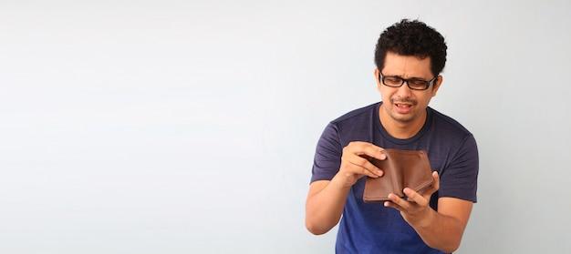 Uomo senza parole scioccato e sorpreso che tiene un portafoglio vuoto su bianco.