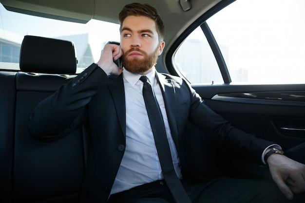 Uomo serio bello di affari che parla sul telefono cellulare