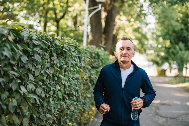 Uomo serio che corre con una bottiglia d'acqua in mano