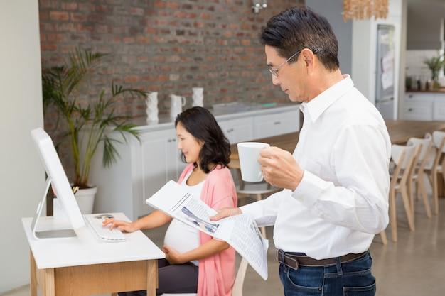 Uomo serio che legge il giornale e che mangia caffè a casa mentre la moglie incinta sta usando il computer portatile